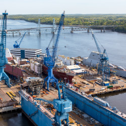 Pictured are two of the three Zumwalt-class stealth destroyers under construction at Bath Iron Works, the DDG 1001, the future USS Michael Monsoor (far left) and the DDG 1000, the future USS Zumwalt (far right), along with the Arleigh Burke-class DDG 115, the future USS Rafael Peralta, in between.