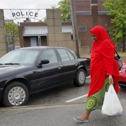 A Somali woman walks past the police headquarters in Lewiston, Maine, June 1, 2015.