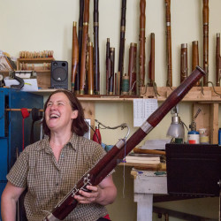 Leslie Ross stops to laugh while playing a modern bassoon on Aug. 11 in her bassoon fabrication studio at her home near the shore of Northern Bay in Penobscot.