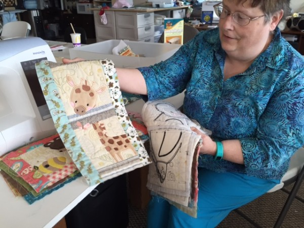 Quilter Deb Norton, co-owner of the A Straight Stitch quilting supply shop, sorts through examples of machine-stitched quilting, applique and embroidery on Aug. 15 at the shop in Orrington. &quotIt's pretty incredible what you can do with machines these days,&quot she said.