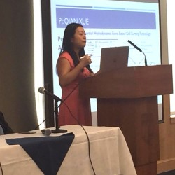 Qian Xue, a professor of mechanical engineering at the University of Maine, explains her research into developing a simple blood-testing device for home-bound Mainers at a recent UMaine forum on aging-related research.