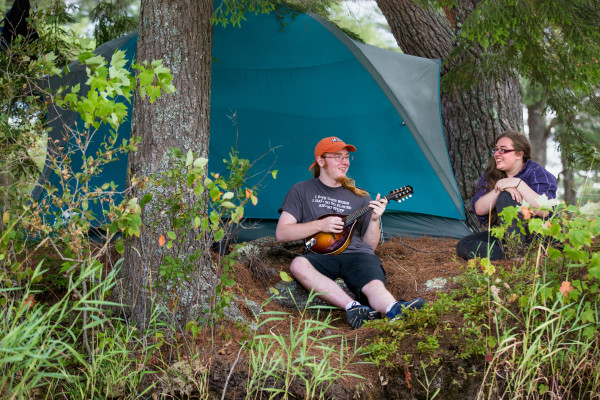 Axel Stewart (left), 19, of Epsom, N.H., plays the mandolin for his sister, Madeleine, while seeking a quiet moment in the trees at Maine Fiddle Camp, a multi-generational summer camp experience that celebrates traditional music in Montville.