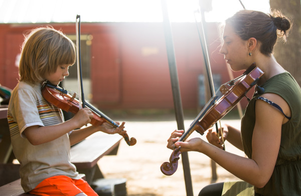 Walden Cutting, 6, of Belfast, practices the fiddle with Maine Fiddle Camp instructor Hannah Otten, 22, of Lewiston, during a meeting of the camp's children's groups, the Eagletts and the Falcons. Fiddle Camp is a multi-generational summer camp experience that celebrates traditional music played under the pine trees.