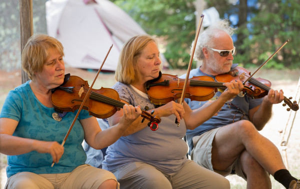 Maine Fiddle Camp attendees take a stab at a new song during some of the practice hours of the multi-generational summer camp that celebrates traditional music played under the pine trees in Montville.