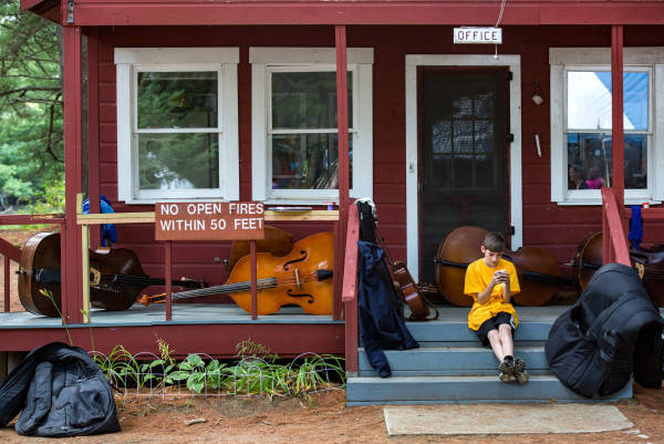 A young boy sits on his phone among basses left unattended at the office building of Maine Fiddle Camp, a multi-generational summer camp experience that celebrates traditional music played under the pine trees in Montville.