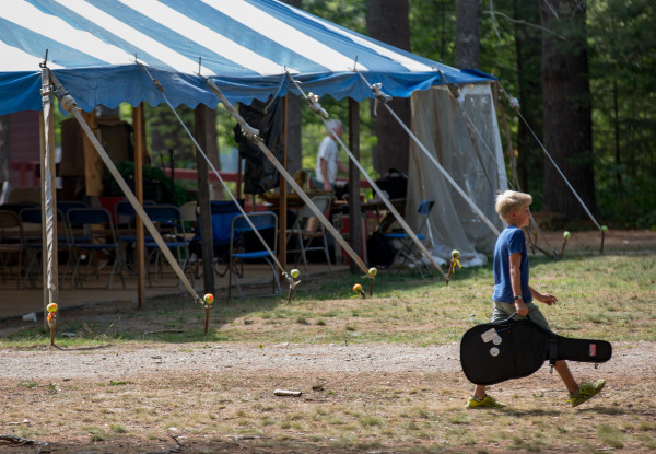 A Maine Fiddle Camp attendee makes his way to an afternoon practice session. The multi-generational summer camp experience celebrates traditional music played under the pine trees.