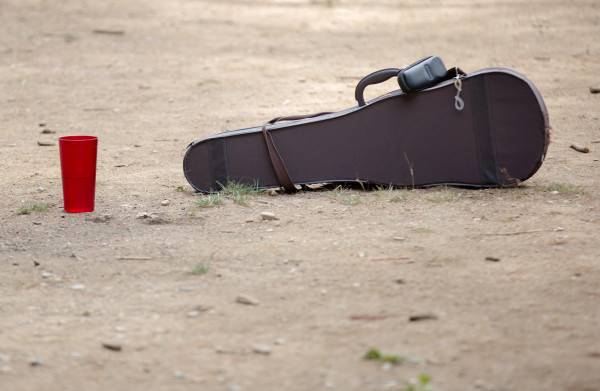 A music case sits unattended in the dirt of the common area at Maine Fiddle Camp, a multi-generational summer camp experience that celebrates traditional music played under the pine trees in Montville.