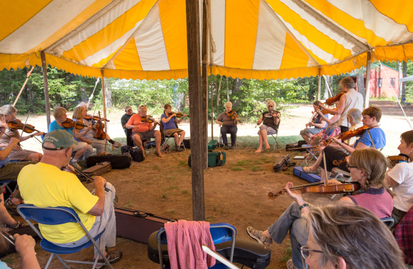 Maine Fiddle Camp attendees practice under one of the many tents in the campground, with people split into groups by skill level. The camp is a multi-generational summer camp experience that celebrates traditional music played under the pine trees.