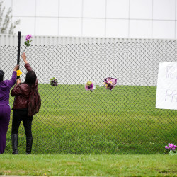 An unidentified employee (left)  of Prince's estate Paisley Park and Prince fan Mona Shelton, 42, of Bloomington, Minnesota,  place flowers on a fence at the Chanhassen, Minnesota, estate,