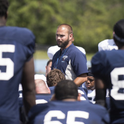 University of Maine football head coach Joe Harasymiak talks to the players after practice on Aug. 8 in Orono. Maine opens Sept. 1 at the University of Connecticut.