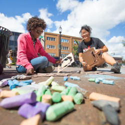 """Tessa Senatus (left) and Victoria Irizarry of the Mansion Church in Bangor go through letter stencils to restart a recently mopped chalk drawing of Bible scripture, nicknamed by the church as """"Sidewalk Scriptures,"""" on Monday in West Market Square in Bangor. The church is behind the sidewalk drawings across the city for the past few months."""