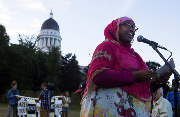Deqa Dhalac, a member of Somali Community Center of Maine, speaks during a rally to show opposition to Gov. Paul LePage Tuesday in Capitol Park, across from the State House, in Augusta. Hundreds of people came out to listen to speakers and show support for LePage resigning from office.