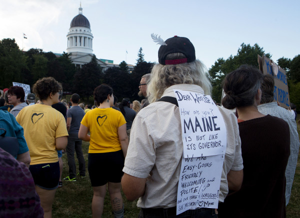 A member of the community wears a sign during a rally to show opposition to Gov. Paul LePage Tuesday in Capitol Park, across from the State House, in Augusta. Hundreds of people came out to listen to speakers and show support for LePage resigning from office.