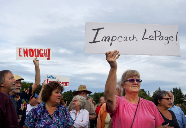 Mary Tracy (right) holds a sign that says &quotImpeach LePage&quot during a rally to show opposition to Gov. Paul LePage Tuesday in Capitol Park, across from the State House, in Augusta. Hundreds of people came out to listen to speakers and show support for LePage resigning from office.