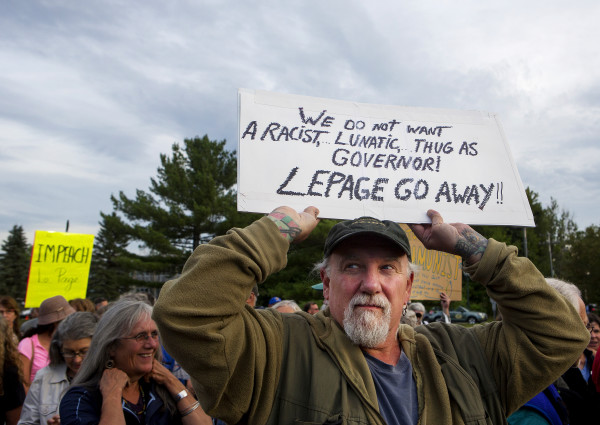 Scott Murray holds a sign above his head during a rally to show opposition to Gov. Paul LePage Tuesday in Capitol Park, across from the State House, in Augusta. Hundreds of people came out to listen to speakers and show support for LePage resigning from office.