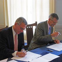 SMCC President Ron Cantor (left) and USM President Glenn Cummings sign documents that simplify and streamline the process for SMCC graduates to transfer to USM.