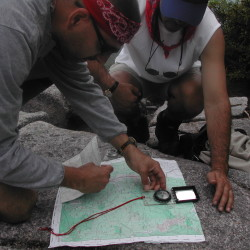 Hikers using a map reading skills to navigate through the Maine woods