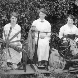 Three women spinning wool to knit socks for soldiers during World War I