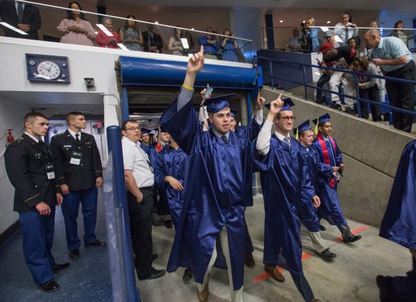 Students from the University of Maine Orono's class of 2016 gesture to the cheers of the crowd upon entering the Alfond Arena during morning graduation ceremonies on May 13.