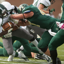 Husson's Ellis Throckmorton (right) tackles Castleton's Moe Harris during their football game at Husson in this October 2015 file photo.
