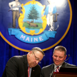 Gov. Paul LePage signs papers on stage at his second inaugural in Augusta on Jan. 7, 2015, with Sen. Mike Thibodeau.