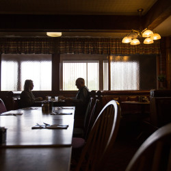 """Connie Higgins (left) and Tim Griffen sit down to breakfast at Bangor's Howard Johnson Restaurant on Tuesday for the restaurant's closing day after 50 years in business. Griffen joked that he'd still come back later in the week just to double check because the restaurant """"sure has had a lot of closing days."""""""