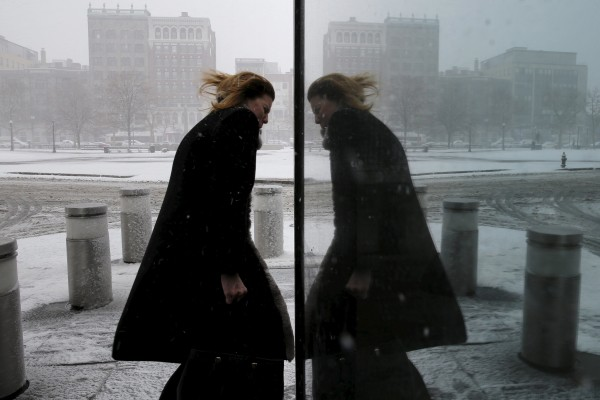 A pedestrian is reflected in an office building as she walks through the wind and snow during a spring snowstorm in Boston, Massachusetts, April 4, 2016.