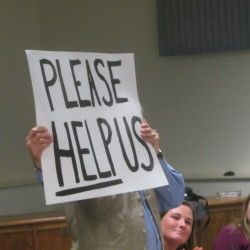 Dr. Ira Mandel held up a poster during a February community forum in Rockland on the heroin crisis.