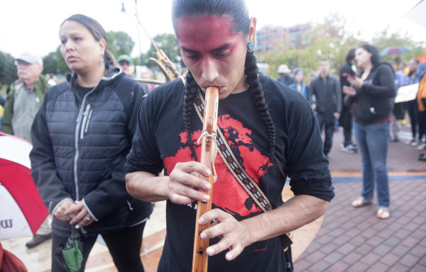 Mye, a Navajo from Arizona, plays the flute before a Sunday event in Bangor showing solidarity with the Standing Rock Sioux Tribe in North Dakota protesting a pipeline construction. Members of Maine Indian tribes and others held the event at the Bangor Waterfront Sunday.
