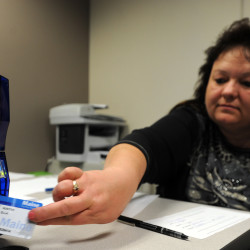 Sue Sapiel, customer service representative at the Department of Health and Human Services Office of Family Independence, prints out a new EBT card that includes a photo in this April 2014 file photo.