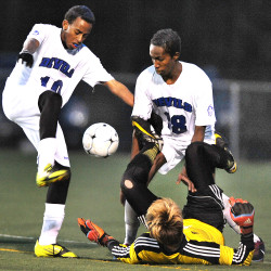 Lewiston's Abdi Shariff-Hassan (left) and Abdulkarim Abdulle (right) miss one of many opportunities to put the ball past Cheverus goalie Jacob Tomkinson during the state championship soccer game at Deering High School in Portland in this November 2014 file photo.