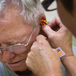 ames Butler (left) grimaces as Marie Arnberg places acupuncture needs in his ear during the Bangor Veterans Acupuncture Clinic at Grace United Methodist Church in Bangor last week.