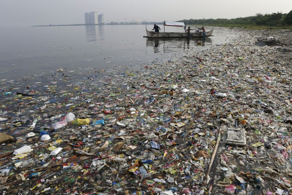 Fishermen prepare to fish amid floating garbage off the shore of Manila Bay on World Oceans Day in 2013.