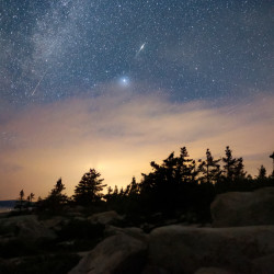 Meteors fall through the night sky over Cadillac Mountain during the annual Perseid meteor shower, as seen from Schoodic Point in Winter Harbor in the early pre-dawn hours, Aug. 12, 2016.