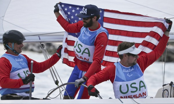 Hugh Freund (middle) of South Freeport and teammates Rick Doerr (left) and Brad Kendell raise the Stars and Stripes after winning the silver medal on Saturday in the Sonar sailing class at the 2016 Paralympic Summer Games in Rio De Janeiro, Brazil.