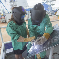 Rosa Maria Peralta etches her initials into the keel plate of the guided-missile destroyer Pre-Commissioning Unit (PCU) Rafael Peralta (DDG 115) in October 2014 with the assistance of Bath Iron Works welder Bob Morey. The ship is named after Marine Corps Sgt. Rafael Peralta, posthumously awarded the Navy Cross for heroism during the Second Battle of Fallujah. Peralta's sisters, Karen Peralta and Icela Peralta Donald also etched their initials into the ship's hull.