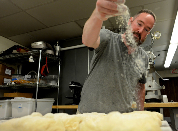 Lee-Russel Dunn is the baker at Fork & Spoon in Bangor. He makes all of the pastries and breads fresh each morning. Dunn sprinkles flour over dough while making ciabatta bread Friday morning.