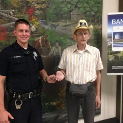 Officer David Farrar (left) hands a Bangor Police Department challenge coin to Bernard Skarda, who along with his wife, Lorraine, alerted authorities after discovering a person who apparently overdosed on heroin inside a bathroom at Bangor City Hall on Sept. 13.
