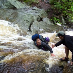 Bryan Courtois (left) crosses a stream in this undated photo.