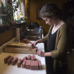 Michelle Byram cuts bars of soap she just took from the mold at SoulShine Soap Co. in Winterport. Byram makes all the soap in her kitchen.
