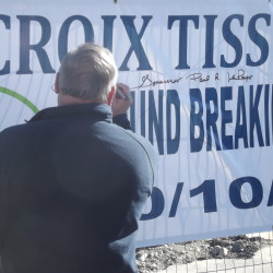 Gov. Paul LePage puts his signature and words of congratulations on a banner at a groundbreaking ceremony for the new St. Croix Tissue mill in Baileyville, Oct 10, 2014.