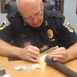 Fort Kent Police Chief Tom Pelletier uses a magnifying glass and flashlight to examine the authenticity of a $20 bill on Wednesday morning.