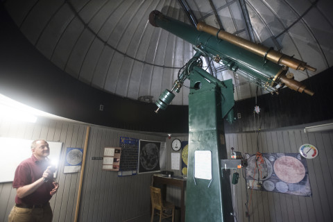 Shawn Laatsch, director of the University of Maine's Emera Astronomy Center, shines a light at the 111-year-old telescope at the Historic Clark Telescope Observatory. The telescope, which was built in the early 1900s, will be moved to a new building and set up for use by next spring.