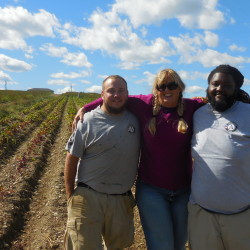 Dixie Shaw (center), director of hunger and relief services for Catholic Charities Maine, poses recently for a photo with James McCall (left) of Jackman and Deante Talbert of Chicago, two of nine AmeriCorps workers from seven states deployed to Aroostook County to help the Farm for ME program harvest crops, in Caribou.