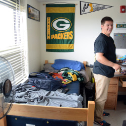 Husson University student Andrew Farnsworth straightens up his dormitory room on Friday. The sports management major said students will welcome the six two-story apartments that will be built on the Bangor campus over the next year.