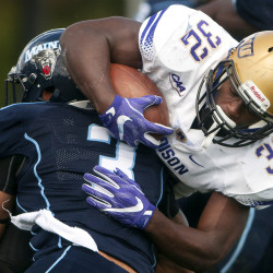 University of Maine's Darrius Hart (left) tackles James Madison's Khalid Abdullah during their football game at Alfond Stadium in Orono Saturday.