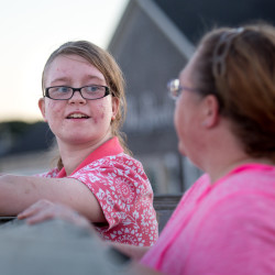 "Ally Beeman, 13, reacts to her ""big"" through the Big Brothers Big Sisters program, Tabitha Fillion, while waiting for sunset at the harbor in Rockland on a brisk evening in mid-September."