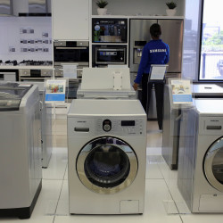 Samsung washing machines are seen as an employee inspects refrigerators at a Samsung display store in Johannesburg, Oct. 3, 2013.