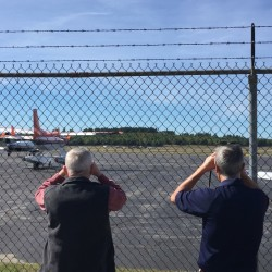 Spectators use their binoculars to see where the small plane landed at Bangor International Airport without its landing gear on Thursday.