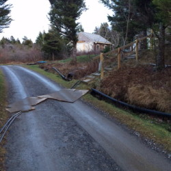 These telephone wires on Monhegan Island were taken down during a Nov. 1, 2014m ice storm and as of Dec. 19, 2014, were still on the road. Fairpoint workers had placed sheets of plywood over the wires so they could be driven on but did not immediately returned to replace two damaged telephone poles.
